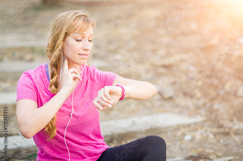 Valokuva Young Fit Adult Woman Outdoors in Workout Clothes Listening To Music with Earphones Checking Her Heart Rate