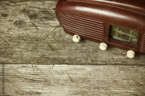 High angle view of old radio standing on the old wooden desk. Edited as a vintage photo with dark edges. Black background. All potential trademarks are removed and blurred.