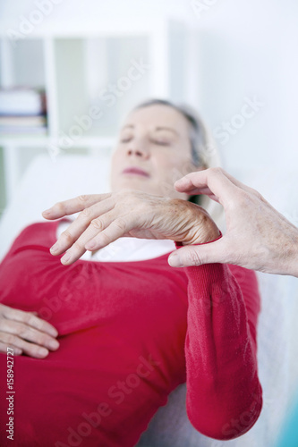 Senior woman undergoing hypnosis session - Buy this stock
