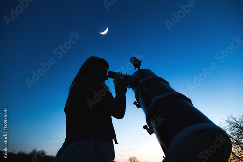Girl looking at the Moon through a telescope. My astronomy work. Fototapeta