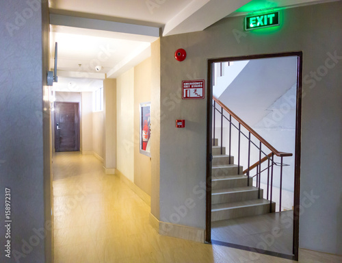 Fototapeta Building Emergency Exit with Exit Sign and Fire Extinguisher