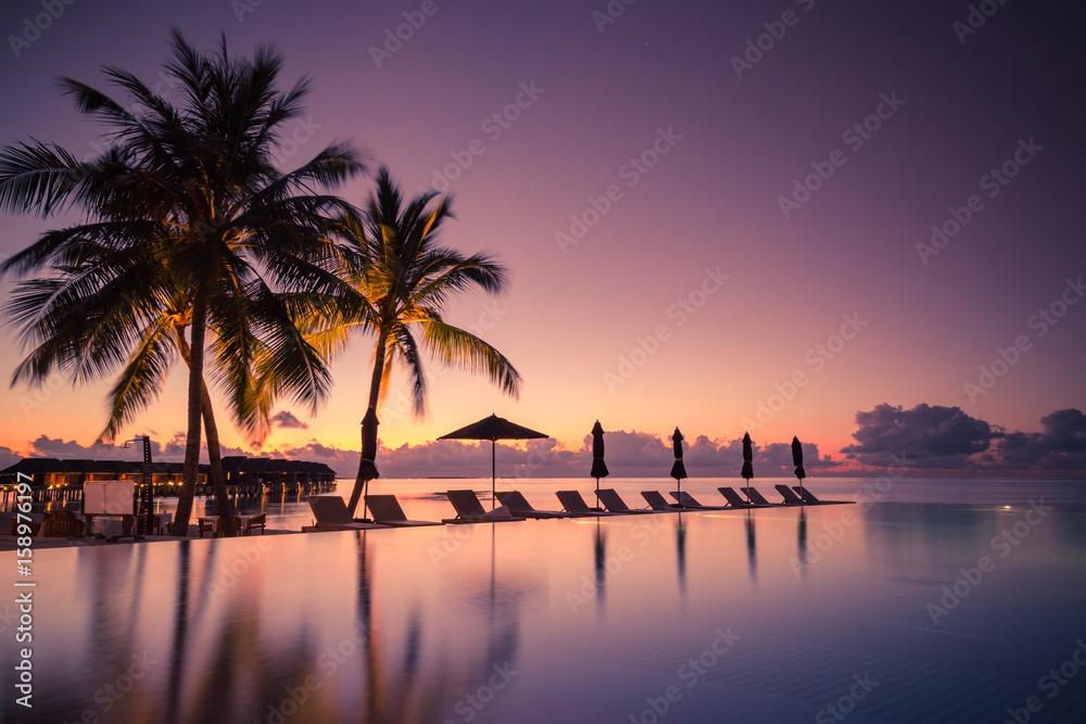 Fototapeta Luxury poolside on the beach with sunset colors. Amazing luxury summer background
