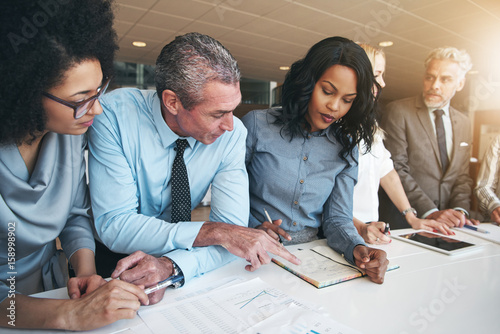 Fotografía  Multiracial workers discussing papers sitting in office