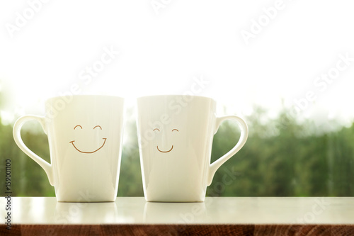 Obraz na plátně Couple of Happy Coffee Mug with smiley face in the morning, Blurred Green Natura