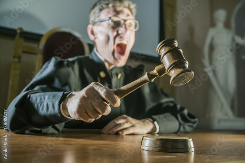 Valokuva  angry man a judge with a hammer in his hand in the court room