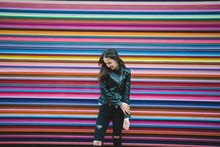 Young Urban Woman And Rainbow Wall