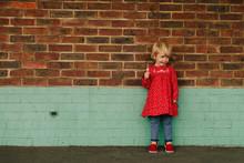 Toddler Girl Against Brick Wall
