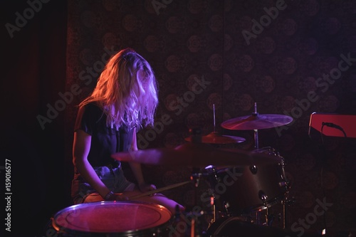 Obraz na płótnie Female drummer performing on illuminated stage