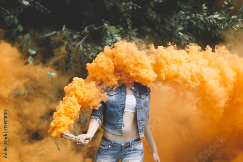 Young woman with orange smoke bomb at the nature Poster