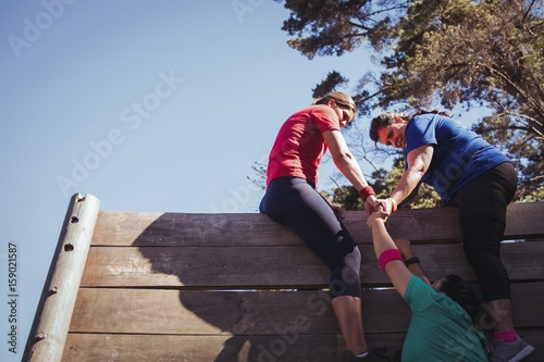 Fotografie, Obraz  Woman being assisted to climb a wooden wall
