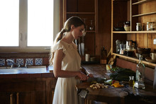 Woman Cooking In A Rustic Log Cabin Kitchen