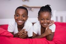 Portrait Of Siblings Lying Tog...