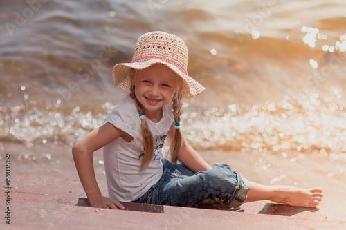 sliczna-usmiechnieta-dziewczyna-z-kapeluszem-na-brzegu-morza