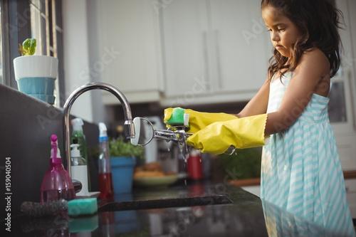 Fotografiet  Cute little girl washing utensil in kitchen sink
