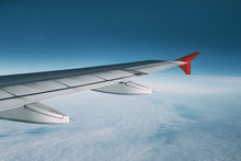 Airplane Wing During A Flight Over A Sky With Clouds