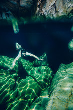 Split Perspective Of A Man Swimming In A Clear Mountain Stream Rockpool