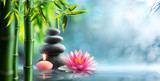 Fototapeta Bambus - Spa - Natural Alternative Therapy With Massage Stones And Waterlily In Water