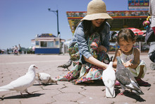 Mother And Daughter Feeding Sea Gulls