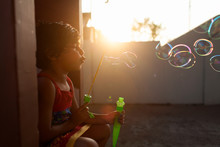 Little Girl Blowing Bubbles At...