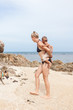Woman Piggybacking Her Son at the Beach
