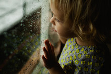 Toddler Girl Looking Out Of Boat Window On A Rainy Day
