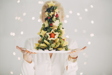 Woman Holding A Christmas Tree Made Of Fruit