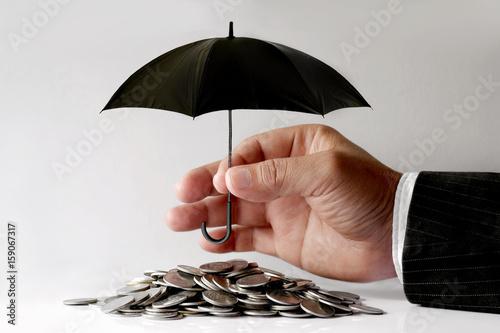 Fototapeta Businessman Protecting Coins With Umbrella. Financial safety Concept. obraz