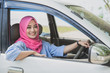beautiful woman wearing hijab smiling while driving a car