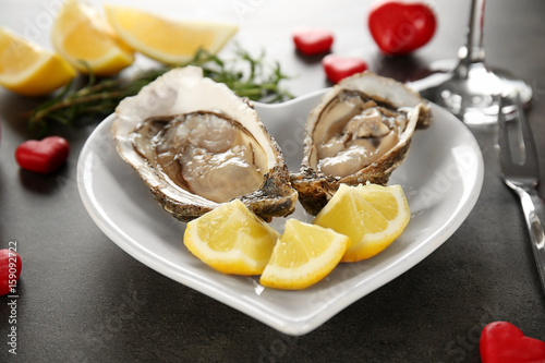 Tasty fresh oysters with sliced lemon on plate in shape of heart. Aphrodisiac food for increasing sexual desire