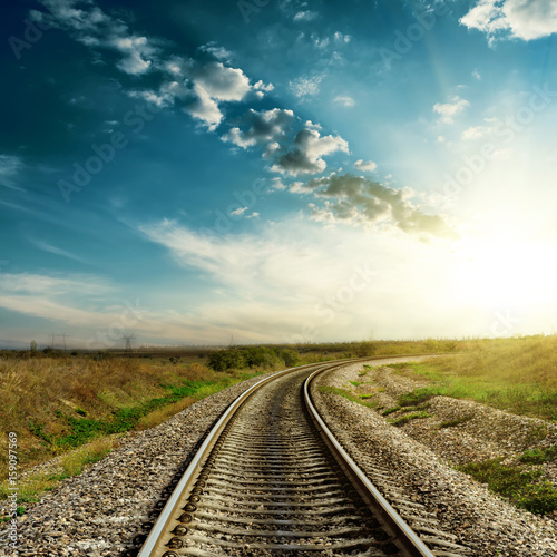 sunset in blue sky over railroad