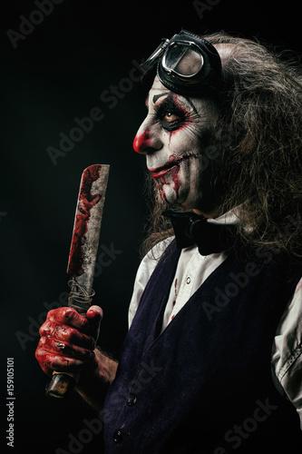 Photo Portrait d'un clown sadique, un couteau ensanglanté dans sa main