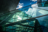 Underside panoramic and perspective view to steel blue glass high rise building with reflections
