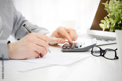 Fotografía  Accountant calculates tax. Working in the office with calculator