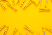 Plastic Clothes Pegs On The Yellow Background With Copy Space