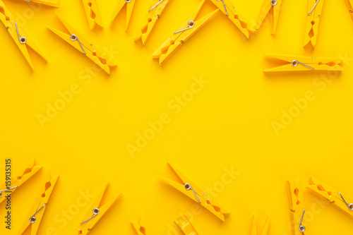 Fotografie, Obraz  plastic clothes pegs on the yellow background with copy space