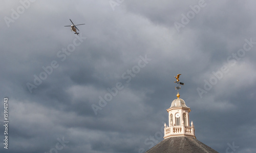 Helicopter Flying Over a Weather Vane on a Cloudy Gloomy