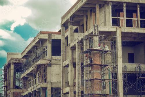 Papiers peints Les vieux bâtiments abandonnés 3 people builders Up scaffolding to plaster the exterior of the building.