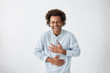 canvas print picture - Positive and joyful Afro American male with fine crop of hair bursting into laughing holding his hands on stomach can`t stopping laughing after hearing funny anecdote. Positive emotions and humour