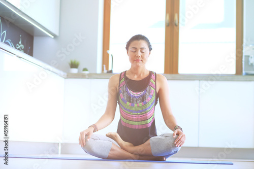 Fotobehang School de yoga Young woman doing yoga at home in the lotus position. Yoga. Woman. Lifestyle