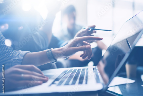 Obraz Business meeting concept.Closeup view of coworkers team working with mobile computer at modern office.Analyze business plans,using laptop.Blurred background.Horizontal.Cropped. - fototapety do salonu