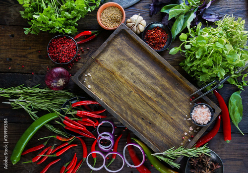 Poster Cuisine Fresh vegetables, spices and herbs on wooden table and empty cutting board in rustic style. Raw organic healthy food concept. Red pepper, onions, garlic, basil and rosemary, top view, space for text