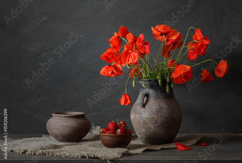 Still life in a rustic style: potteries, strawberry and a bouquet of red poppies