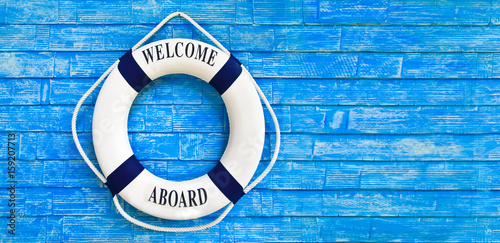 Fototapeta  White color Life buoyancy with welcome aboard on it hanging on blue wall