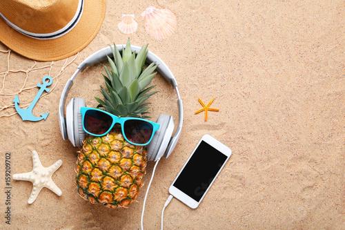 Ripe pineapple with sunglasses and headphones on beach sand