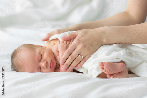 Newborn baby sleeping on a blanket. Mother gently strokes her child's hand