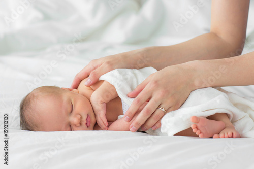 Photo  Newborn baby. Mother gently strokes her child's hand