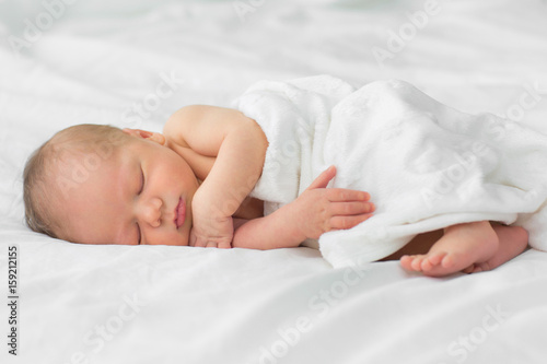 Photo  Newborn baby sleeping on a blanket. Age 1 week