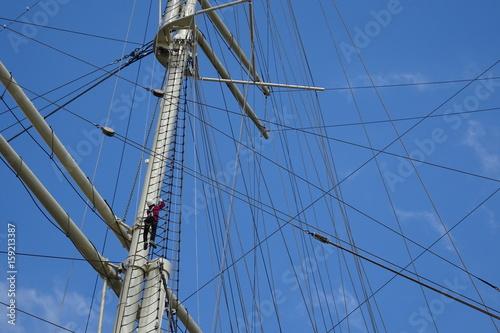 Mutiges Klettern in den Seilen eines Segelschiffes vor blauem Himmel © Katilia