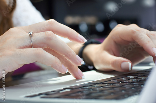 Fototapeta Cropped image of young woman hands typing on laptop computer in coffee shop. Business woman using laptop computer.Freelance concept. obraz na płótnie