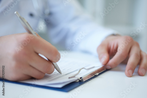 Male medicine doctor hand holding silver pen writing something on clipboard closeup Canvas Print
